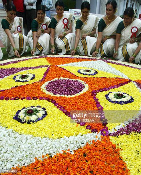 Southern Indian women dressed in traditional attire pose in front of a traditional flower arrangement called 'Pookalam' during Onam celebrations in...