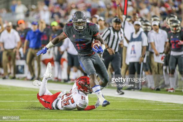 Southern Methodist Mustangs running back Ke'Mon Freeman leaps over Arkansas State Red Wolves linebacker Trent EllisBrewer during the game between SMU...