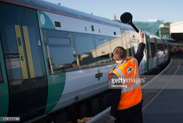 A Southern Railway Ltd employee signals to the driver of a passenger train from a platform at Clapham Junction rail station in London UK on Tuesday...