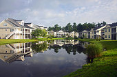 Background with a modern neighborhood with buildings around the pond. Houses and trees reflected in the tranquil water during beautiful cloudy morning in South Carolina, USA.