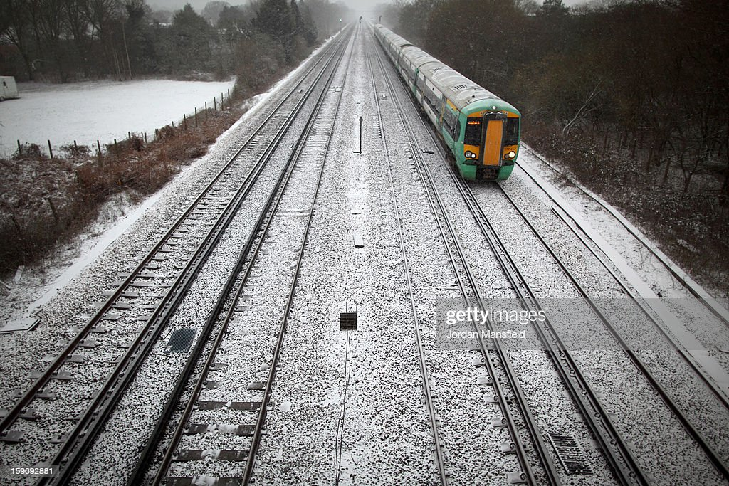 A Southern service train passes through Crawley on January 18, 2013 in Crawley, United Kingdom. Widespread snowfall is affecting most of the UK with school closures and transport disruption. The Met Office has issued a red weather warning for parts of Wales, advising against all non-essential travel as up to 30cm of snow is expected to fall in some areas today.