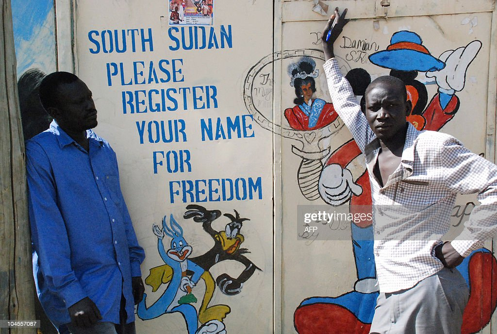 Southern Sudanese artists stand next to a painted sign urging people to register for the upcoming independence referendum in the southern capital of...