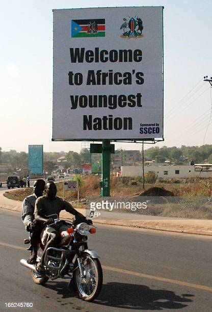 Southern Sudanese men ride a motorcycle past a billboard celebrating the choice of the south to separate Africa's largest nation in two in the...