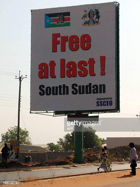 Southern Sudanese walk under a billboard celebrating the choice of the south to separate Africa's largest nation in two in the southern Sudanese...