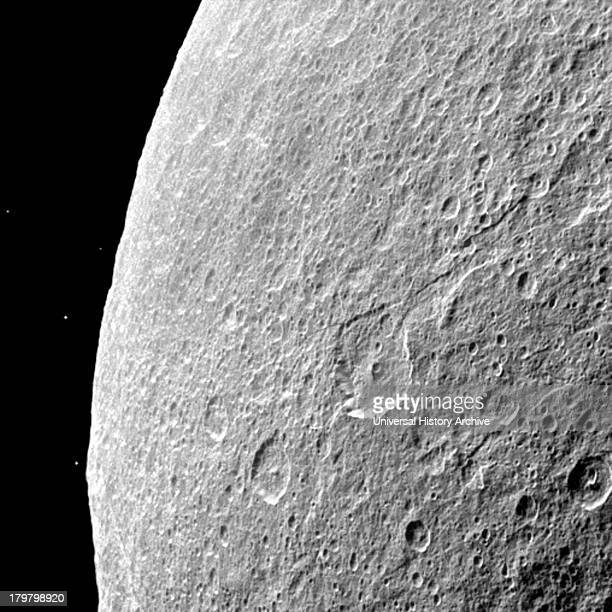 Southern terrain on Saturn's moon Rhea is dimly illuminated by Saturnshine in this Cassini spacecraft view of the dark side of the moon