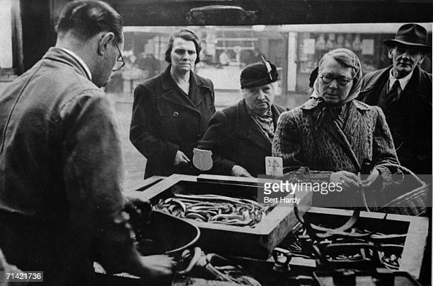 Southwark residents buying jellied eels from a stall at the Elephant and Castle in South London 8th January 1949 Original Publication Picture Post...