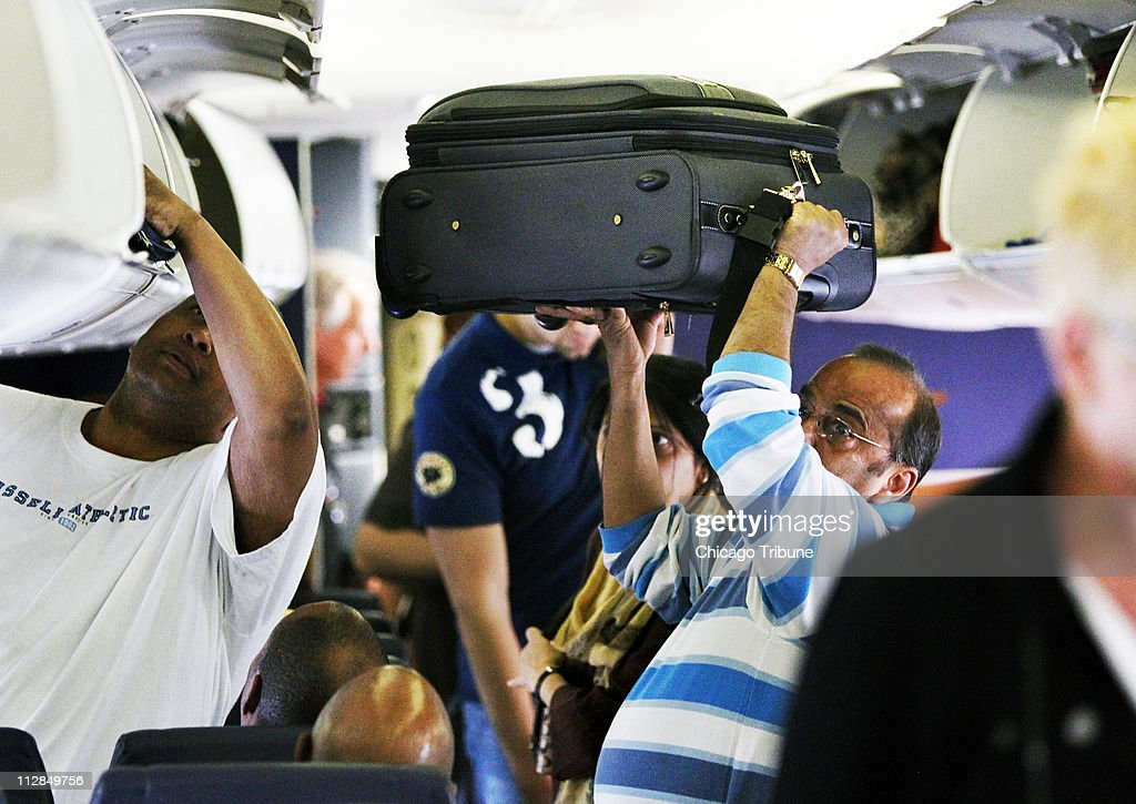 A Southwest Airline passenger lifts his luggage into the air while looking for a storage spot in the overhead compartments before a flight from Midway Airport in Chicago to Cleveland, Ohio, April 2, 2010.