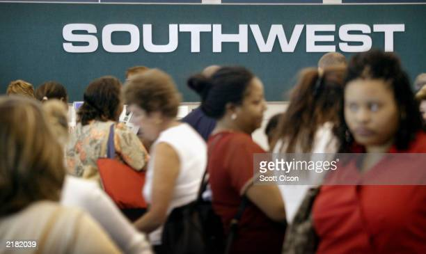 Southwest Airlines passengers wait in line at the ticket counter July 21 2003 at Midway Airport in Chicago Illinois Southwest reported a net income...
