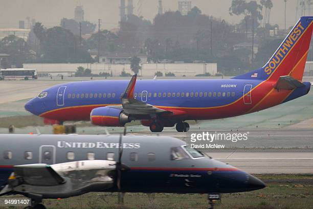 Southwest airplane taxies as a United Express takes off at Los Angeles International Airport after a snow storm on the East Coast caused the...