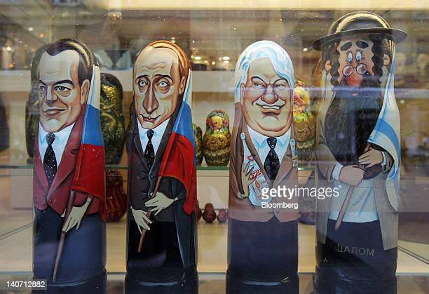 Souvenir babushka dolls depicting Russian political leaders left to right Dmitry Medvedev Vladimir Putin and Boris Yeltsin stand in a store window in...