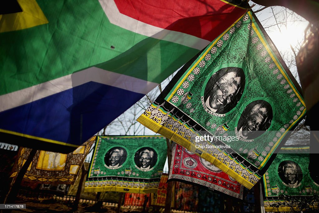 Souvenir flags picturing former South African President Nelson Mandela sway in the wind across from the Hector Pieterson Memorial and Museum in Soweto Township June 24, 2013 in Johannesburg, South Africa. South African President Jacob Zuma confirmed that Mandela's condition has become critical since he was admitted to the hospital over two weeks ago for a recurring lung infection.