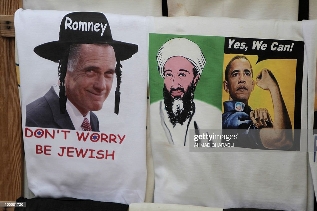 A souvenir shop in Jerusalem's old city displays t-shirts for sale among them one of US Republican presidential candidate Mitt Romney wearing a Jewish Orthodox hat (L) and one of US President Barak Obama under his 2008 campaign slogan next to a portrait of assassinated al-Qaeda leader Osama Ben Laden, on November 6, 2012. AFP PHOTO/AHMAD GHARABLI
