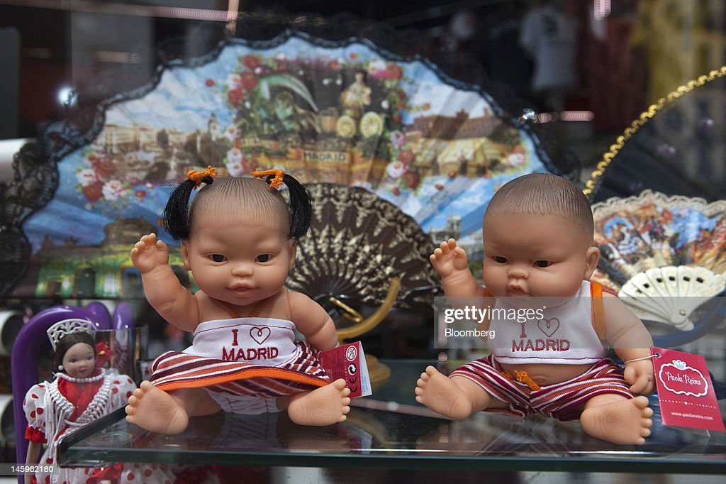 Souvenir toy dolls wearing 'I love Madrid' tops stand for sale on a shelf in a tourist store in Madrid, Spain, on Friday, June 8, 2012. Spain is poised to become the fourth of the 17 euro-area countries to require emergency assistance as the currency bloc's finance chiefs plan weekend talks on a potential aid request to shore up the nation's lenders. Photographer: Angel Navarrete/Bloomberg via Getty Images