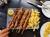 souvlaki greek etnic food mear roasted in a plate wiht lemon and potatoes
