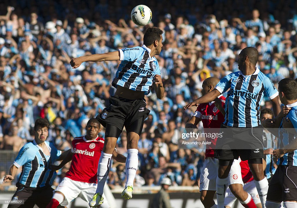 Souza and Naldo of Gremio struggle for the ball with Igor of Internacional during a match between Gremio and Internacional as part of the Brasilian Championship Serie A at Olimpico Stadium on December 02, 2012 in Porto Alegre, Brazil.