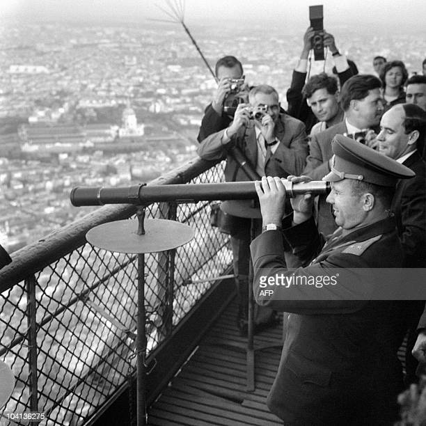 Soviet Cosmonaut Yuri Gagarin looks through a telescope as he visits the Eiffel Tower 28 September 1963 in Paris He became the first human to travel...