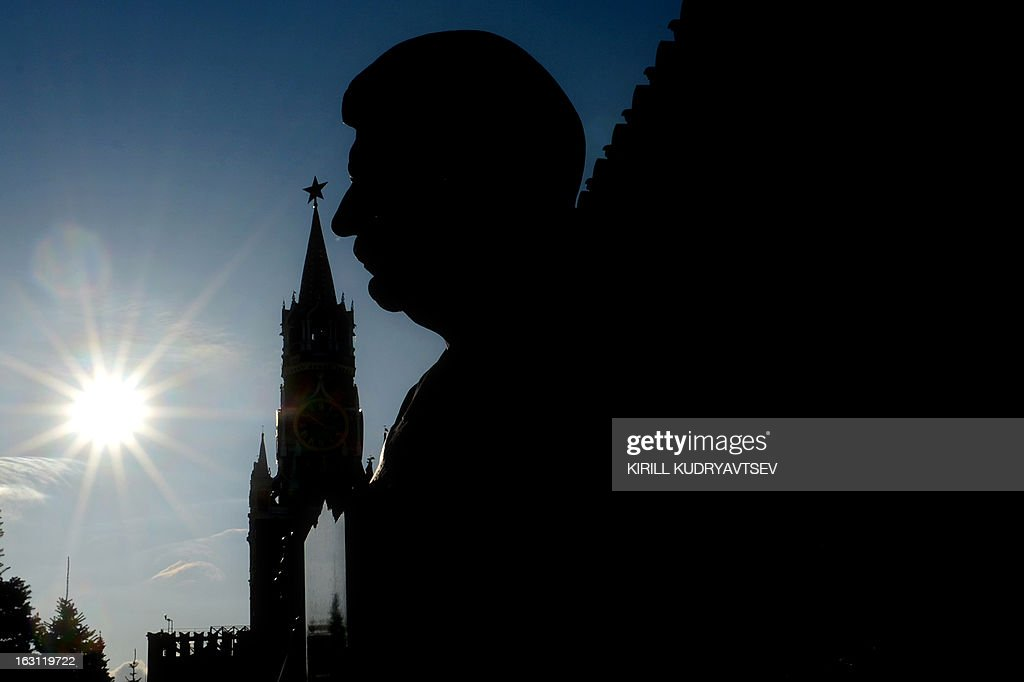 Soviet dictator Josef Stalin's bust at his tomb and the Kremlin's Spasskaya (Saviour) Tower are silhouetted against the sky at the Red Square in Moscow on March 5, 2013. Russia marks today 60 years since the death of Stalin with attitudes split about whether to view him as a tyrant who slaughtered millions or a national saviour who helped turn the country into a global superpower that emerged victorious in World War II.