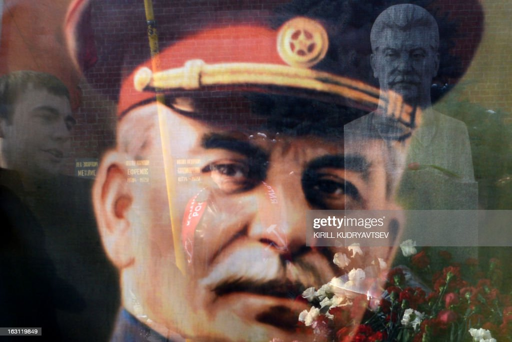 Soviet dictator Josef Stalin's bust at his tomb (R) is seen through a transparent portrait of a Stalin at the Red Square in Moscow on March 5, 2013, as Russian Communists and their supporters pay tribute to the Soviet dictator on the 60th anniversary of his death. Russia marks today 60 years since the death of Stalin with attitudes split about whether to view him as a tyrant who slaughtered millions or a national saviour who helped turn the country into a global superpower that emerged victorious in World War II.