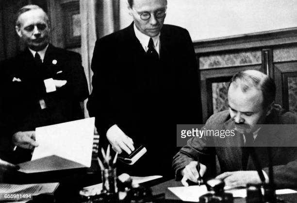 Soviet Foreign Minister Vyacheslav Molotov flanked by German Nazi Foreign Minister Joachim Von Ribbentrop signs the SovietGerman NonAggression Pact...