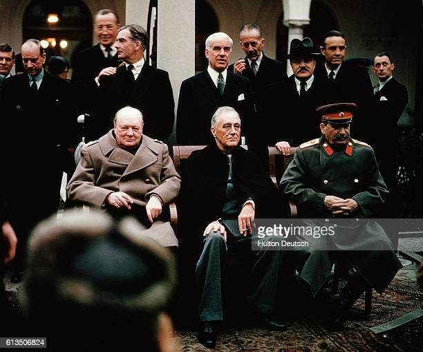 Soviet leader Stalin American President Roosevelt and British Prime Minister Churchill seated together during the Yalta Conference 1945 Behind them...