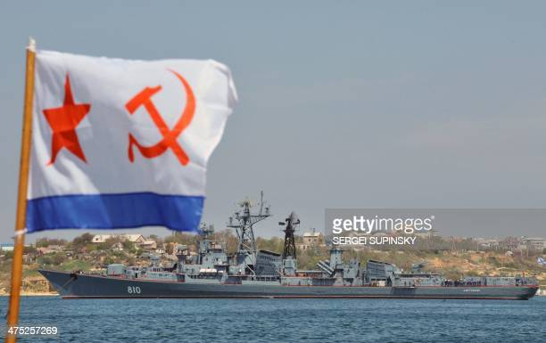 A Soviet Navy flag waves on a pleasure boat as it passes in front of a Russian Navy vessel prepared for the Victory Day parade in the bay of...
