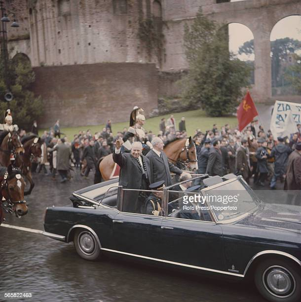 Soviet politician and Chairman of the Presidium of the Supreme Soviet Nikolai Podgorny pictured waving from the rear of a limousine with President of...