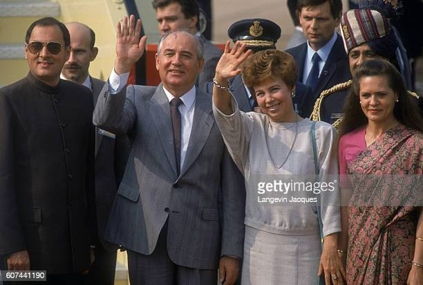 Soviet President Mikhail Gorbachev and his wife Raisa wave during a departure ceremony as part of a state visit to India To the right is Indian Prime...
