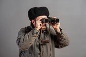 Soviet soldier with binoculars on guard, retro uniform. Second World War theme