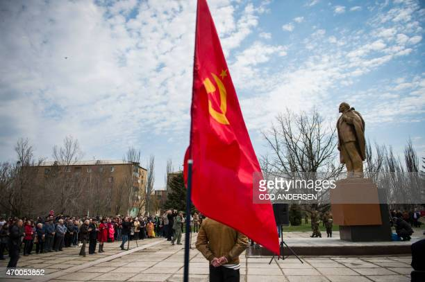 A Soviet Union flag is displayed as people attend the unveiling of a Lenin statue in the town of Novoazovsk on April 17 2015 in the selfproclaimed...