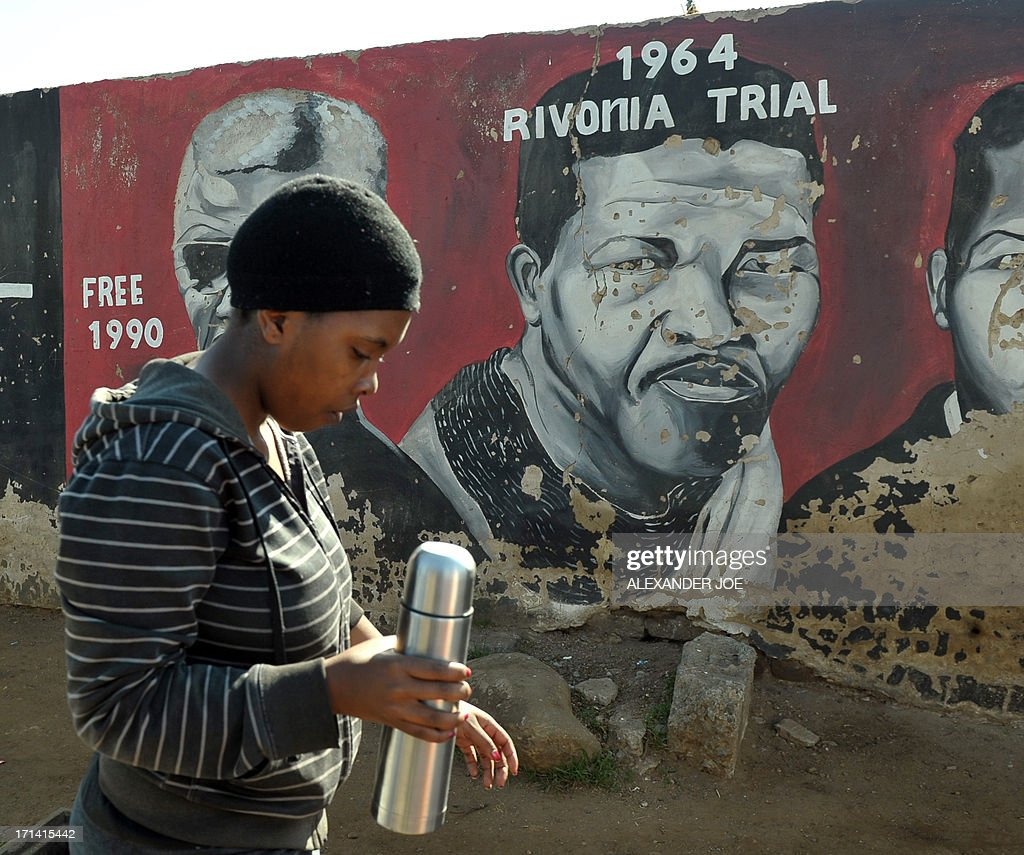 A Soweto resident is pictured near paintings of anti-apartheid icon Nelson Mandela in Soweto, where Mandela once lived, on June 24, 2013. A statement issued by the South African government reported that former South African president Nelson Mandela's health was in a critical stage after his condition in hospital worsened over the course of 24 hours.