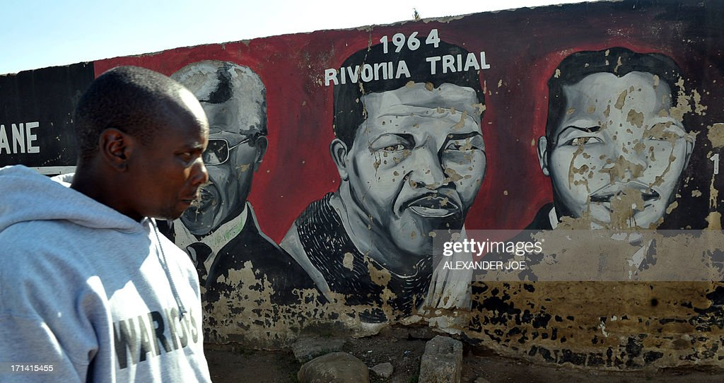 A Soweto resident is pictured near paintings of anti-apartheid icon Nelson Mandela in Soweto, where Mandela once lived, on June 24, 2013. A statement issued by the South African government reported that former South African president Nelson Mandela's health was in a critical stage after his condition in hospital worsened over the course of 24 hours. AFP PHOTO / ALEXANDER JOE
