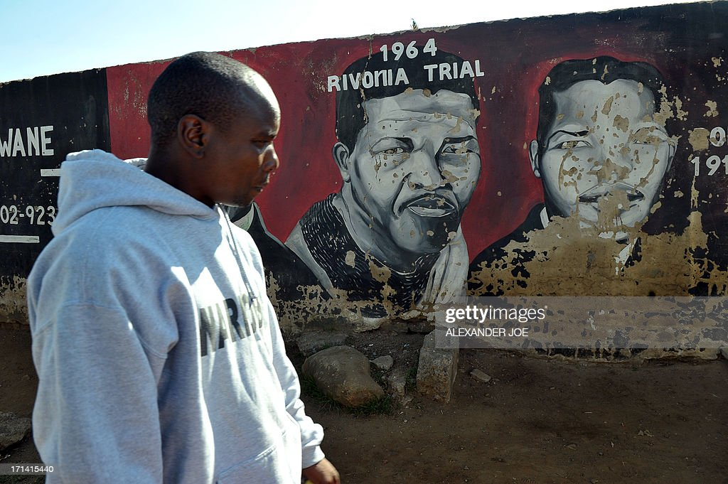 A Soweto resident is pictured near pantings of anti-apartheid icon Nelson Mandela in Soweto, where Mandela once lived, on June 24, 2013. A statement issued by the South African government reported that former South African president Nelson Mandela's health was in a critical stage after his condition in hospital worsened over the course of 24 hours. AFP PHOTO / ALEXANDER JOE