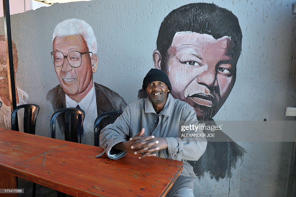 A Soweto resident, waits for his food in a restaurant under a painting of Nelson Mandela in Soweto on June 24, 2013. Anti-apartheid icon Nelson Mandela remained in a critical condition in hospital on June 24, 2013 leaving millions in South Africa and across the world fearing the worst. JOE
