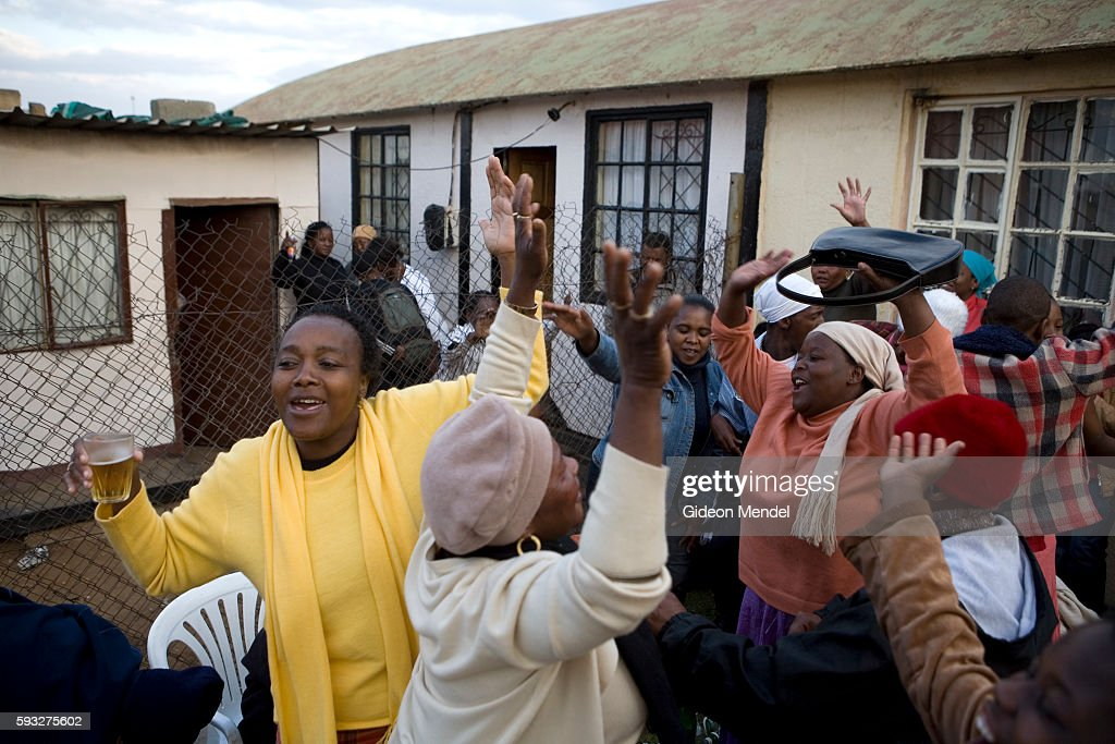 Soweto residents dance drink and sing church songs at a special ceremony and celebration held to honour the ancestral spirit of a family member of...