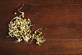 Many small soy bean sprouts isolated on side of textured rustic wooden table surface, top view