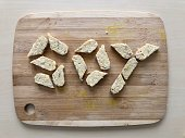 Chunks of tempeh, the vegetarian soy cake, spelling out the word SOY in all capital letters on a bamboo cutting board