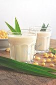 Soy milk in glass cup decorated by soybean and pandan leaf on wooden table background.