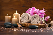 Spa setting with brown rolled towel, orchids and candles on wood. Relaxing spa concept with candles, towels and hot stones massage with himalayan pink salt. Beautiful composition for beauty treatment