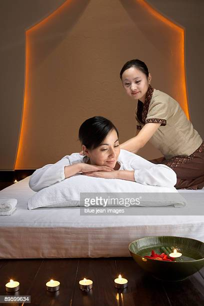 Spa attendant massaging woman
