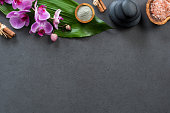 Top view of spa setting with hot stones, orchids and pink salt. High angle view of orchids with green leaf on blackboard with stacked hot stone for massage treatment. Luxury and elegant spa set with c