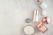 Spa beauty products on white marble table from above. Coconut oil, high-end cream, serum,  perfume, candles. Beauty blog concept. Copy space