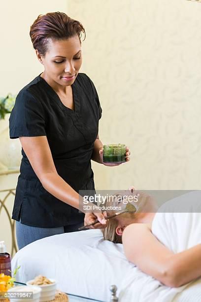 Spa estheticial appliquant la crème pour le visage du client pendant le visage