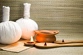 Spa herbal compressing ball with candle and incense on mat background