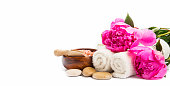 Spa setting with pink peonies, cotton towels , massage stones isolated