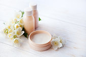 Spa setting with beauty cream and white  flower
