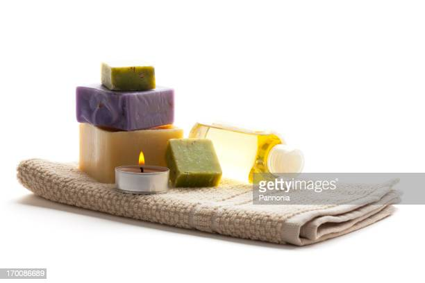 Spa setting with candle, towel, soaps and bottle