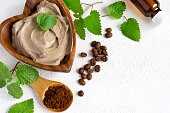 Spa setting with cosmetic clay mask for body, Towel  Essential oil and coffee beans