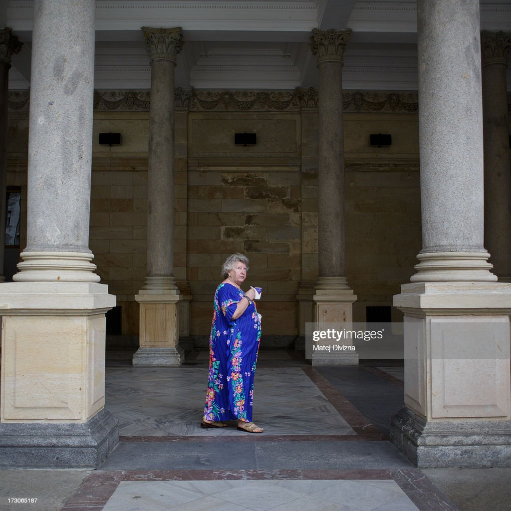 A spa tourist walks through colonnade and drinks healing spring during the 48th Karlovy Vary International Film Festival (KVIFF) on July 05, 2013 in Karlovy Vary, Czech Republic.