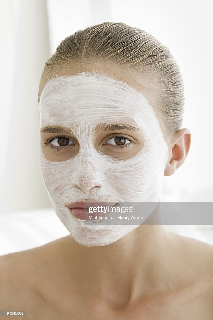 A spa treatment centre. A young woman with a white facial mask on her skin. : Stock Photo