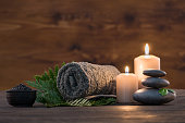 Brown towel on green fern with candles and black hot stone on wooden background. Hot stone massage setting lit by candles. Hot stone therapy for one person with candle light. Beauty spa treatment and